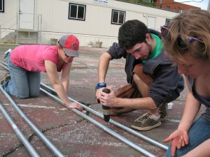 SUST majors Maria (left) and Conor help Chicago Lights farm manager Lauralyn put together a hoop house pole, May 2012 (Photo: A. Mayes)