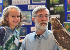Rob Sulski shows a red-tailed hawk to a young conference-goer in 2011(Photo: Jason Steger)
