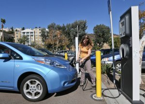 Angie Vorhies charged her electric car in San Diego in 2013. The city has committed to using 100 percent renewable energy, becoming the largest American municipality to do so. (Credit: Lenny Ignelzi/Associated Press)