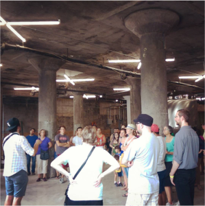 Brian Taylor (left), owner of Whiner Brewing, showing the brewery to a tour group. This space has been changing the most recently and is now producing beer. Notice the reused florescent lights. (Photo: E. Rhea)