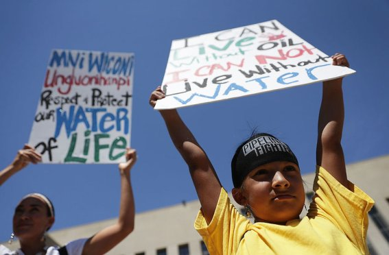 "WASHINGTON, DC - AUGUST 24: Seven-year-old Omaka Nawicakinciji (R) of the Oglala Lakota Nation in South Dakota participates with his mother Heather Mendoza (L) during a rally on Dakota Access Pipeline August 24, 2016 outside U.S. District Court in Washington, DC. Activists held a rally in support of a lawsuit against the Army Corps of Engineers ""to protect water and land from the Dakota Access Pipeline,"" and to call for ""a full halt to all construction activities and repeal of all pipeline permits until formal tribal consultation and environmental review are conducted."" (Photo by Alex Wong/Getty Images)"